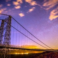 Lights shine along highway 50 beneath the Royal Gorge Bridge at dusk.